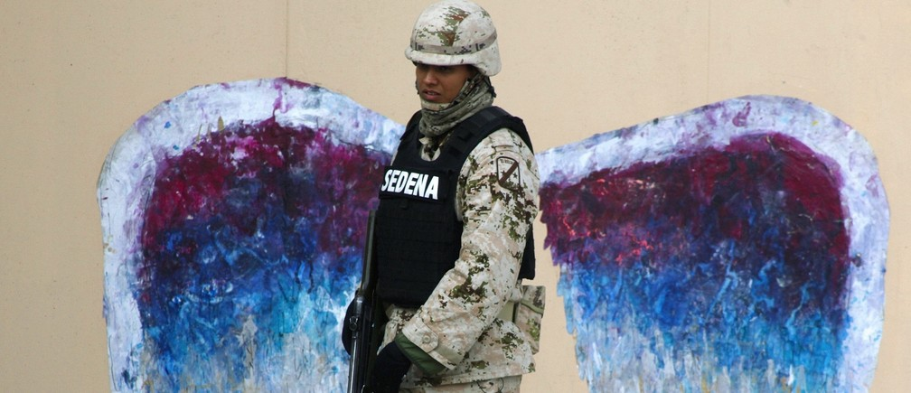 A soldier walks past graffiti depicting angel wings by artist Colette Miller in Ciudad Juarez, Mexico