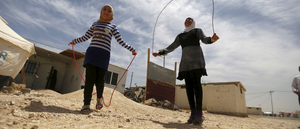 Syrian refugee Omayma al Hushan (R), 14, who launched an initiative against child marriage among Syrian refugees, plays with her friend outside their residence in Al Zaatari refugee camp in the Jordanian city of Mafraq, near the border with Syria, April 21, 2016.