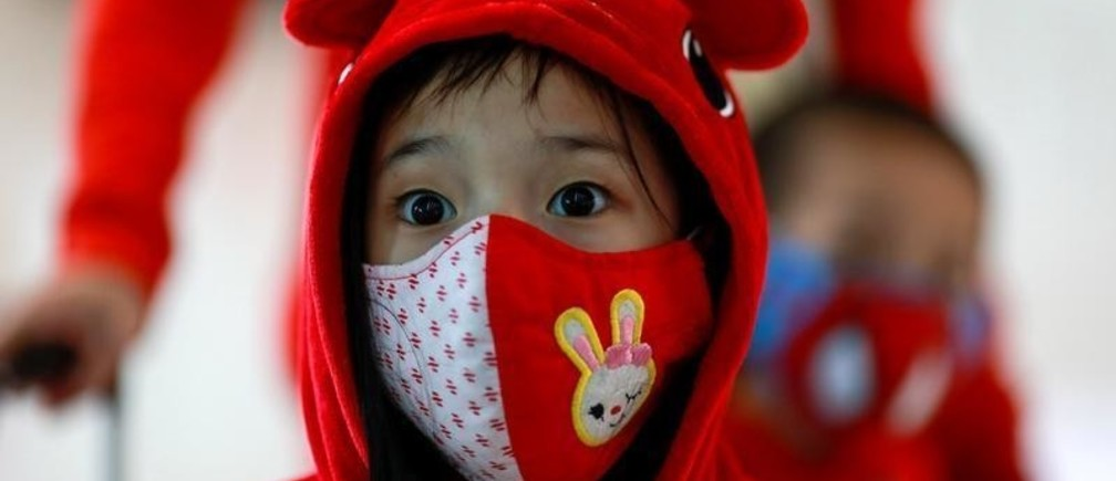 A child wears a mask to prevent the spread of the new coronavirus as they arrive at Suvarnabhumi Airport in Bangkok, Thailand February 3, 2020. REUTERS/Soe Zeya Tun - RC2WSE963UTM