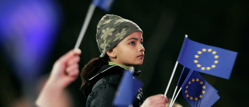 A girl attends a concert, surrounded by European Union flags, during celebrations marking the 50th anniversary of the founding Treaty of Rome at the Brussels' Atomium, March 24, 2007.