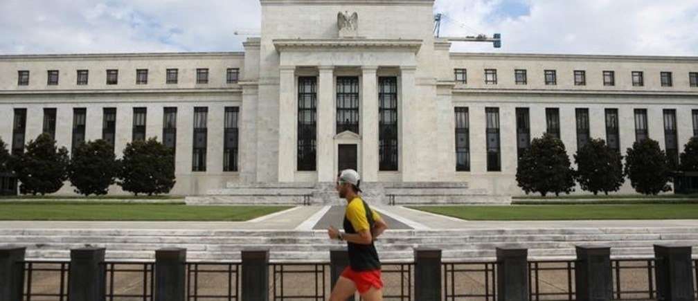 A jogger runs past the Federal Reserve building in Washington, DC, U.S., August 22, 2018. REUTERS/Chris Wattie