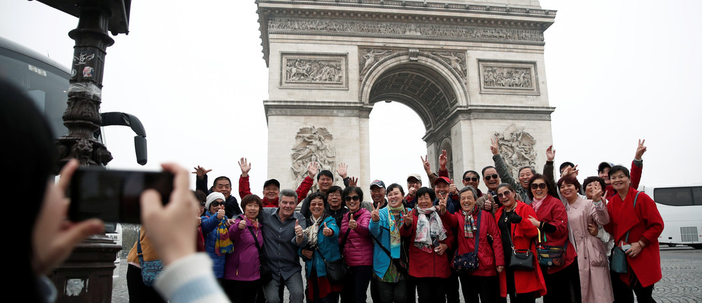 "Chinese tourists pose for photos in front of the Arc de Triomphe on the Champs-Elysees avenue during the Act XIX (the 19th consecutive national protest on a Saturday) of the ""yellow vests"" movement in Paris, France, March 23, 2019. REUTERS/Benoit Tessier - RC1CAD5A0980"