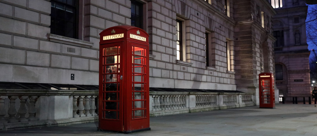 Red telephone boxes stand in an empty street in Whitehall in London, Britain March 12, 2020.