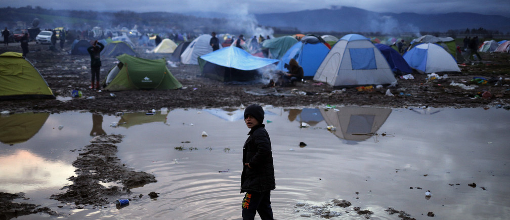 A migrant boy stands in a puddle in a makeshift camp on the Greek-Macedonian border, near the village of Idomeni, Greece March 10, 2016.