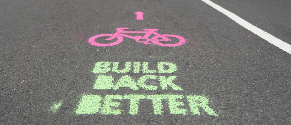 A cyclist cycles by painted stencils on a street to create pop up bike lanes in preparation for distanced bike rides, following the outbreak of the coronavirus disease (COVID-19), London, Britain, May 16, 2020. REUTERS/Peter Nicholls - RC2PPG9C9JNC