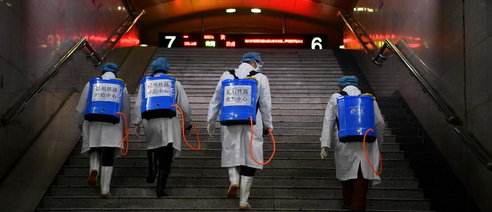 Des travailleurs avec un équipement de désinfection montent un escalier alors qu'ils désinfectent une gare tandis que le pays est touché par une épidémie du nouveau coronavirus, à Kunming, province du Yunnan, Chine, le 4 février 2020.