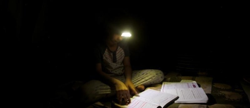A girl uses a headlight as she studies at home during continued blackout in Sanaa, Yemen April 26, 2019. REUTERS/Mohamed al-Sayaghi - RC1D93B83C80