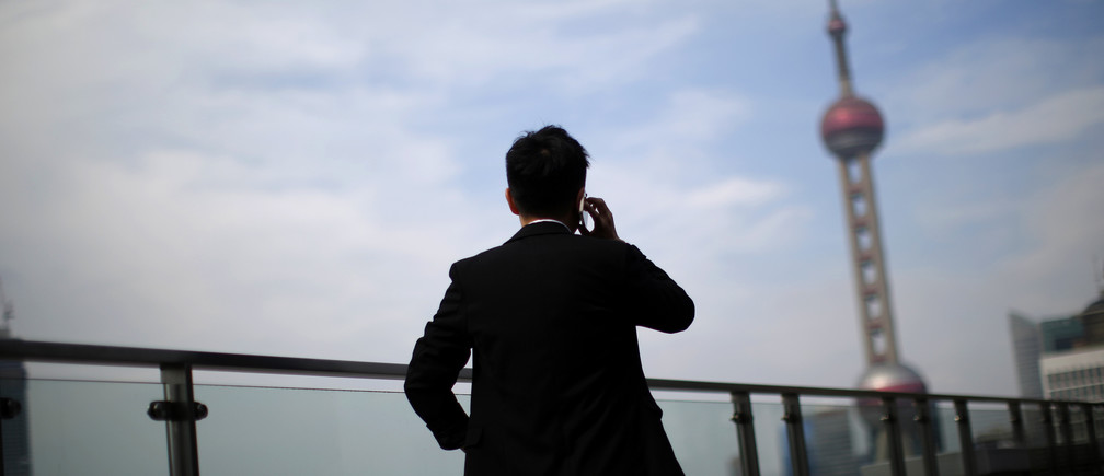 A man talks on a mobile phone near the Pudong financial district in Shanghai July 17, 2014.