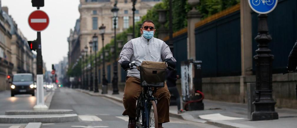 Un hombre con una mascarilla monta en bicicleta en la Rue de Rivoli en París durante el brote de la enfermedad coronavirus (COVID-19) en Francia, el 5 de mayo de 2020.