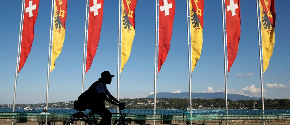 A cyclist passes flags of Switzerland and the Canton of Geneva along the shore of Lake Geneva on a warm and sunny day in Switzerland September 9, 2016.