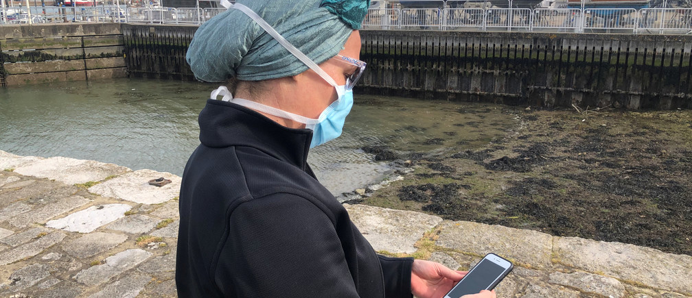 UK National Health Service employee Anni Adams looks at new NHS app to trace contacts with people potentially infected with the coronavirus disease (COVID-19) being trialled on Isle of Wight, Britain, May 5, 2020. Picture taken May 5, 2020. REUTERS/Isla Binnie - RC2JIG9TVG6M