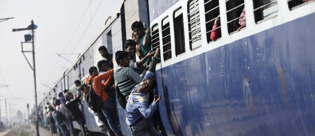 Passengers travel in an overcrowded train near a railway station at Loni town.