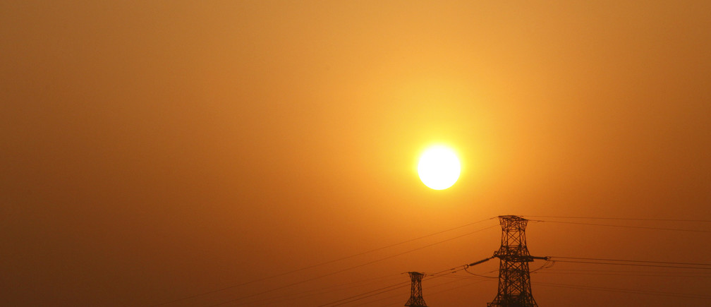 The sun rises behind electricity pylons in Beijing