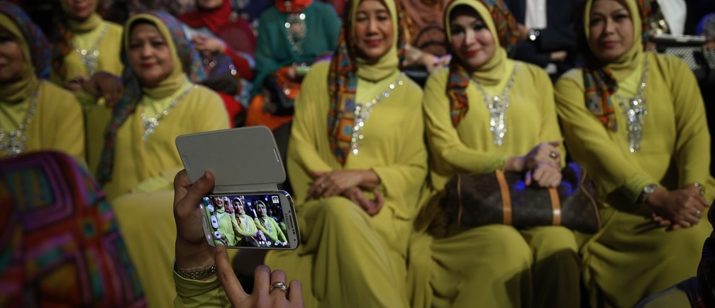 Members of the audience pose for a photo during the third Annual Award of World Muslimah in Jakarta September 18, 2013.