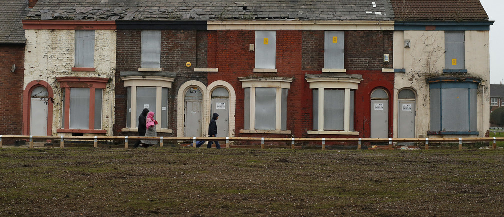People walk past a row of boarded up terraced houses in the Kensington area of Liverpool, northern England February 20, 2013. REUTERS/Phil Noble