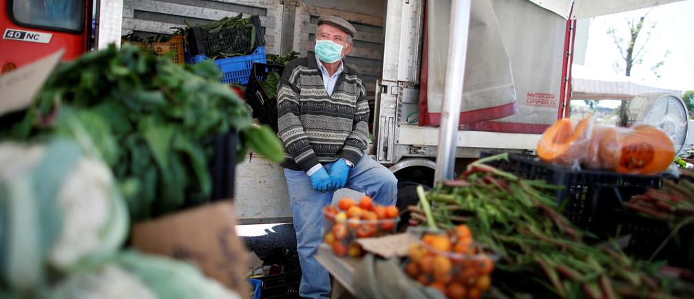 Un vendedor con una máscara protectora se sienta en su puesto en un mercado de alimentos al aire libre que ha sido reabierto, durante el brote de la enfermedad coronavirus (COVID-19) en Cisternino, Italia, el 27 de abril de 2020.