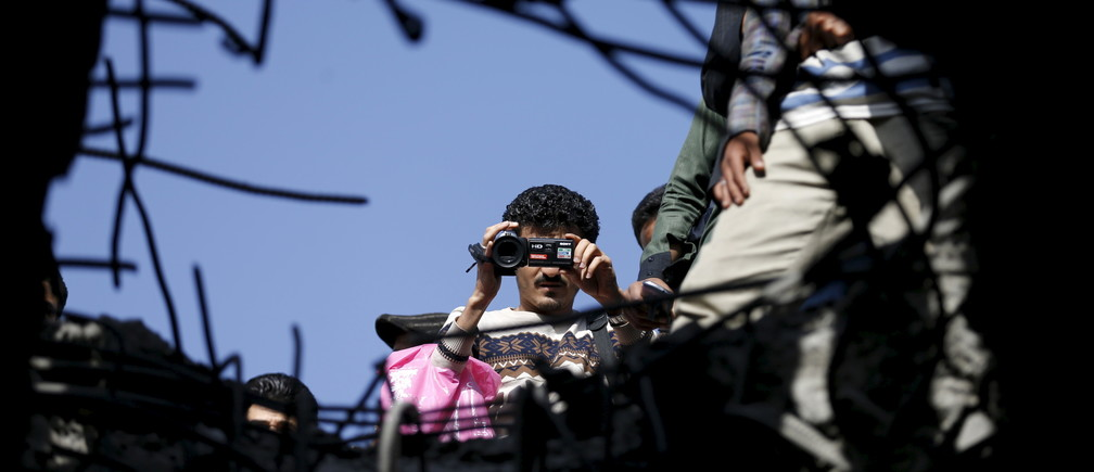 A journalist films the site of a Saudi-led air strike on a bridge in Yemen's capital Sanaa March 23, 2016.