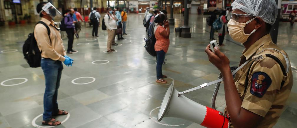 Un funcionario de la policía ferroviaria hace un anuncio por altavoz en el que dice a los viajeros que se pongan de pie dentro de los círculos designados para mantener el distanciamiento social mientras esperan para abordar un tren en una estación de ferrocarril después de que se levantaran algunas restricciones durante un cierre para frenar la propagación de la enfermedad coronavírica (COVID-19) en Mumbai (India), el 22 de junio de 2020.