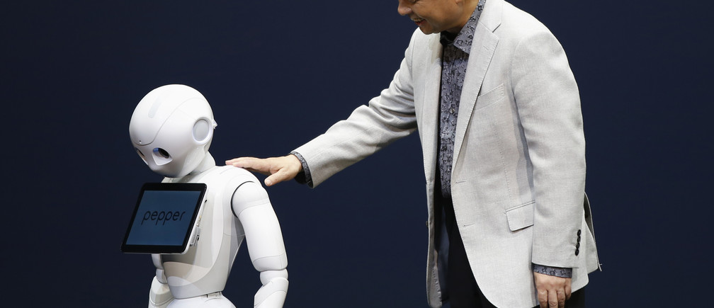 SoftBank Corp. Chief Executive Masayoshi Son (R) presents the company's human-like robots named 'pepper' during a news conference in Urayasu, east of Tokyo June 5, 2014. Japan's SoftBank Corp unveiled the human-like robots which it will use to staff its cellphone stores and personal usage at a home, in a move aimed at expanding the mobile phone and Internet conglomerate's technological reach. Son announced the plan at a news conference on Thursday, the robot will go on sale to public in Japan from February 2015, which price is about 198,000 yen. Softbank will use technologies developed by French robotics company Aldebaran, in which it took a stake in 2012. REUTERS/Issei Kato (JAPAN - Tags: SCIENCE TECHNOLOGY BUSINESS TELECOMS SOCIETY) - GM1EA6512JP01
