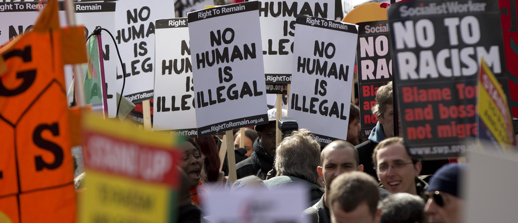 People hold placards during a Stand up to Racism and Fascism rally in central London March 22, 2014. REUTERS/Neil Hall (BRITAIN - Tags: SOCIETY CIVIL UNREST) - LM1EA3M18SM01