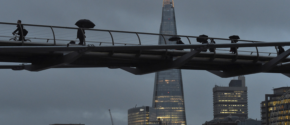 City workers cross the Millennium footbridge at dawn in front of the Shard skyscraper, in the financial district of London, Britain January 7, 2016.