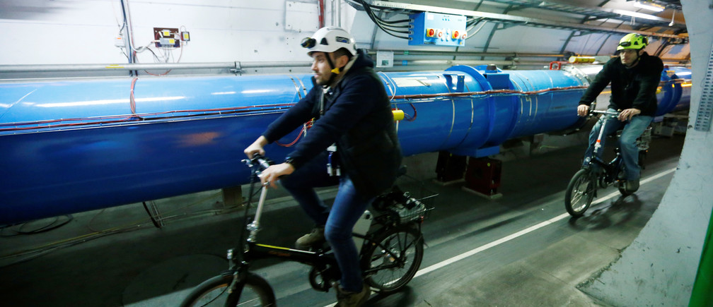 Scientists cycle along the Large Hadron Collider tunnel.