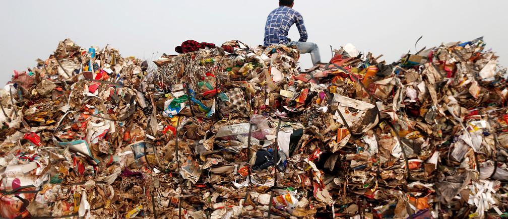 A man sits atop a pile of discarded polythene and plastic sheets at a recycling yard in New Delhi, India, November 22, 2018