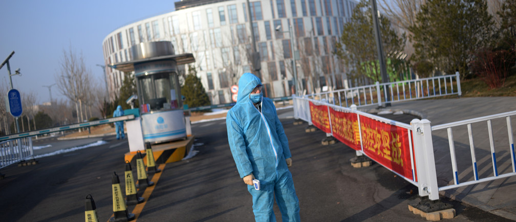 A security guard wearing a protective suit and a face mask stands as he holds a thermometer in front of the entrance to the China Transinfo Technology Co,in the morning after the extended Lunar New Year holiday caused by the novel coronavirus outbreak, in Zhongguancun Software Park, in Beijing, China February 10, 2020. REUTERS/Tingshu Wang - RC2GXE9XNYHB