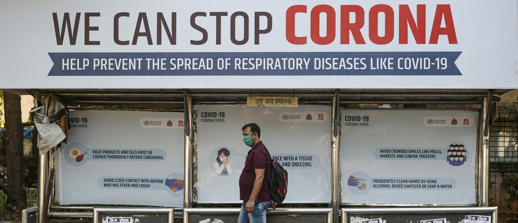 A man wearing a protective mask walks past a bus stop displaying preventive measures against the coronavirus in Mumbai, India, March 18, 2020. REUTERS/Francis Mascarenhas - RC2BMF9GGPRU