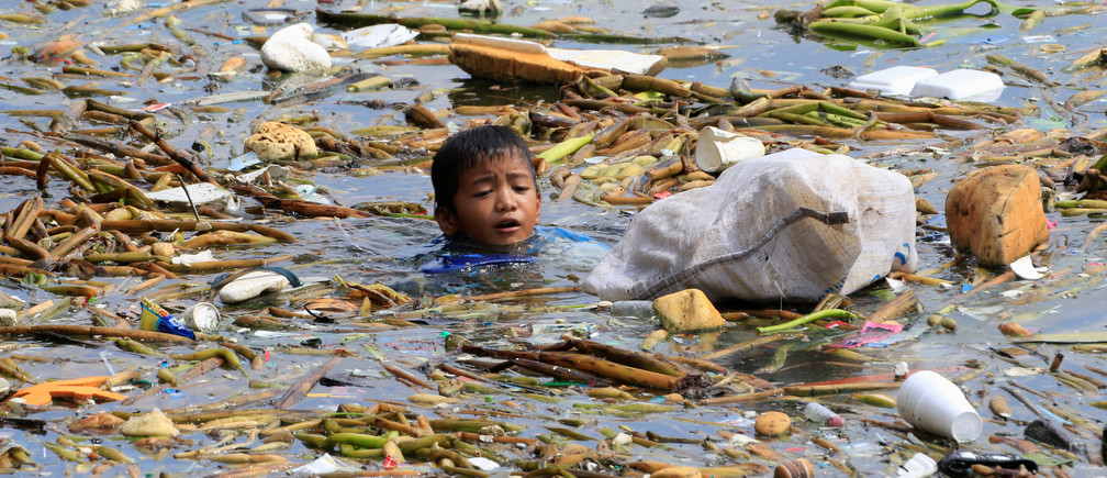 A boy swims as he collects recyclable plastic bottles drifting with garbage along the coast of Manila Bay at the slum area in the Baseco Compound in metro Manila, Philippines October 16, 2017. REUTERS/Romeo Ranoco - RC1E8CAB9C40
