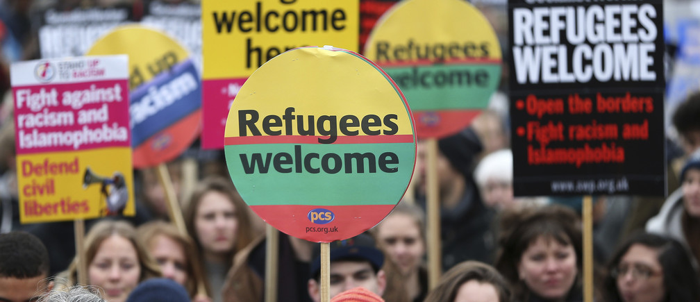 Demonstrators hold placards during a refugees welcome march in London, Britain March 19, 2016.  REUTERS/Neil Hall  - LR1EC3J17M3Y0