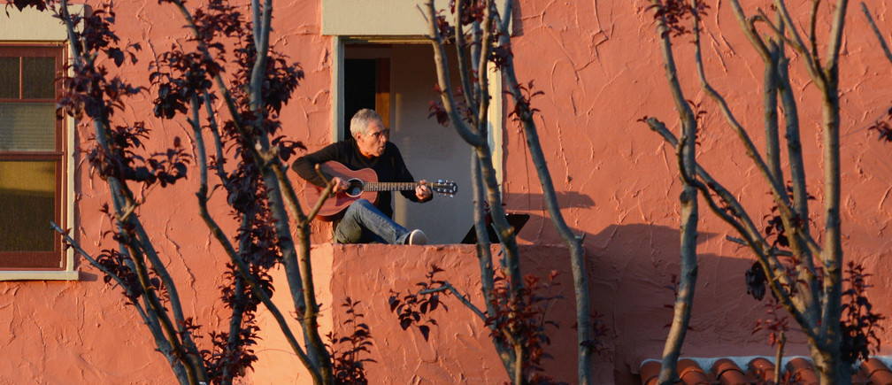 "Danny Wertheimer plays guitar and sings to his neighbors from his balcony two days after California's Governor Gavin Newsom implemented a state wide ""stay at home order"" directing the state's 40 million residents to stay in their homes for the foreseeable future in the face of the fast-spreading coronavirus disease (COVID-19) in Oakland, California, U.S. March 21, 2020. Picture taken March 21, 2020. REUTERS/Kate Munsch     TPX IMAGES OF THE DAY - RC2APF9BXFUG"