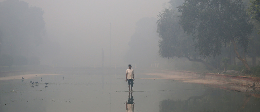 A man walks in a pond on a smoggy morning in New Delhi, India, October 31, 2016