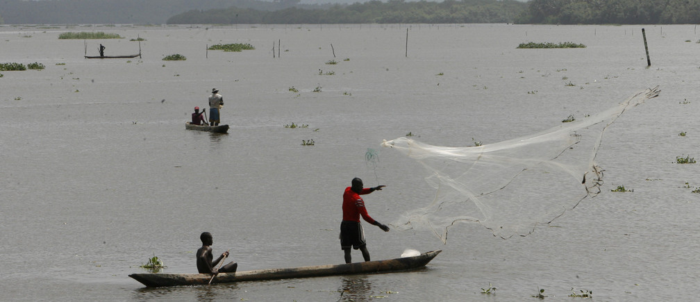 A fisherman casts his net from his boat in the lagoon of Grand Lahou in southern Ivory Coast June 8, 2010. REUTERS/Luc Gnago