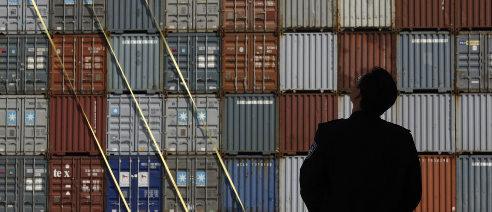A security guard stands in front of columns of containers at the Yantian International Container Terminal (YICT) in the southern Chinese city of Shenzhen in Guangdong province November 25, 2008.  REUTERS/Bobby Yip   (CHINA) - GM1E4BP1T8101