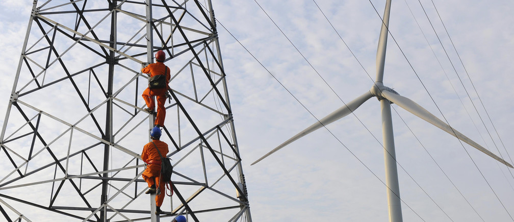 Employees climb up an electricity pylon next to a windmill to carry on a routine inspection at a wind power plant in Mingguang, Anhui province July 8, 2013. Picture taken July 8, 2013. REUTERS/China Daily (CHINA - Tags: BUSINESS ENVIRONMENT ENERGY TPX IMAGES OF THE DAY) CHINA OUT. NO COMMERCIAL OR EDITORIAL SALES IN CHINA - GM1E9790W6U01