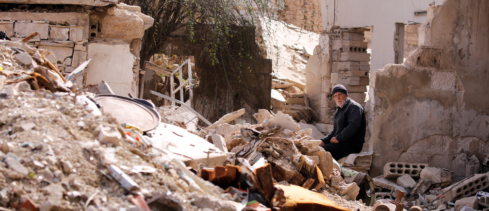 A man sits near rubble of damaged buildings in Ein Terma, a district of eastern Ghouta, Syria February 26, 2019.  Picture taken February 26, 2019. REUTERS/Omar Sanadiki - RC1C1C8F8280