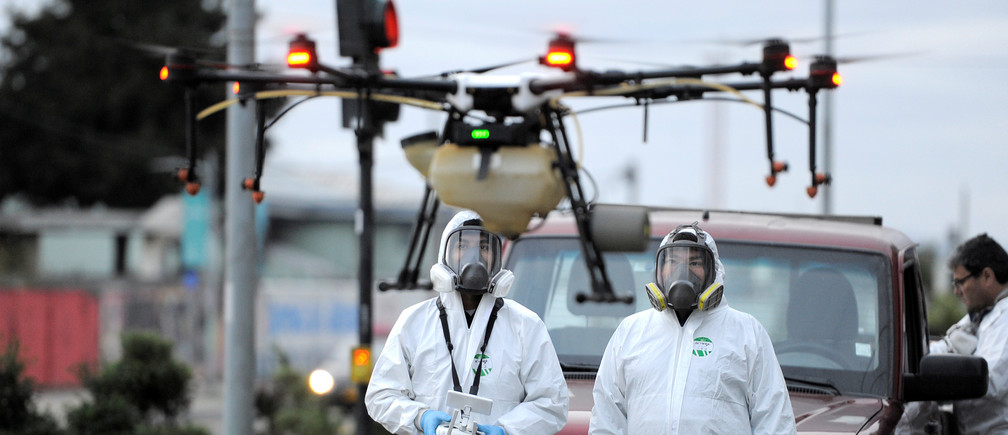 Local community workers use a drone loaded with disinfectant to released on streets during the coronavirus disease (COVID-19) outbreak in Talcahuano, Chile March 21, 2020. REUTERS/Jose Luis Saavedra - RC2JOF9IBZQT