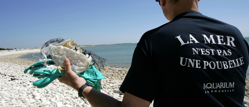 "Marine biologist Pierre Moriniere from the La Rochelle Aquarium wears a shirt that reads ""The Sea is Not a Trash Bin"" as a volunteer holds plastic webbing debris from the beach, La Rochelle, France, June 8, 2005. They are participating in a campaign to heighten public awareness about non-biodegradeable waste on World Ocean Day on France's Atlantic coast"