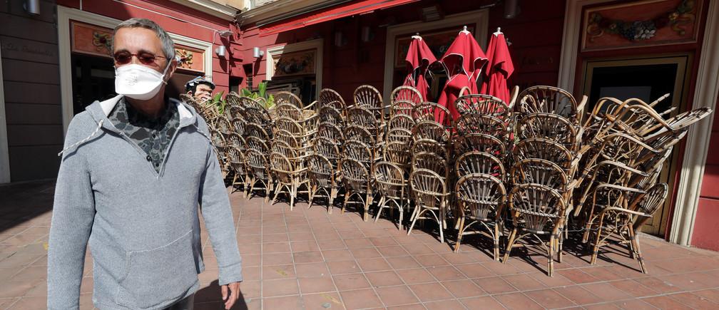 Un homme portant un masque facial protecteur passe devant les chaises empilées d'un restaurant fermé à Nice, alors qu'un confinement est imposé pour ralentir le taux de la maladie à coronavirus (COVID-19) en France, le 14 avril 2020.