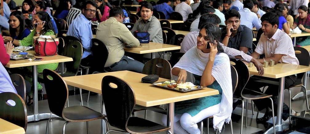 An employee speaks on a mobile phone as she eats her lunch at the cafeteria in the Infosys campus in the southern Indian city of Bangalore September 23, 2014.