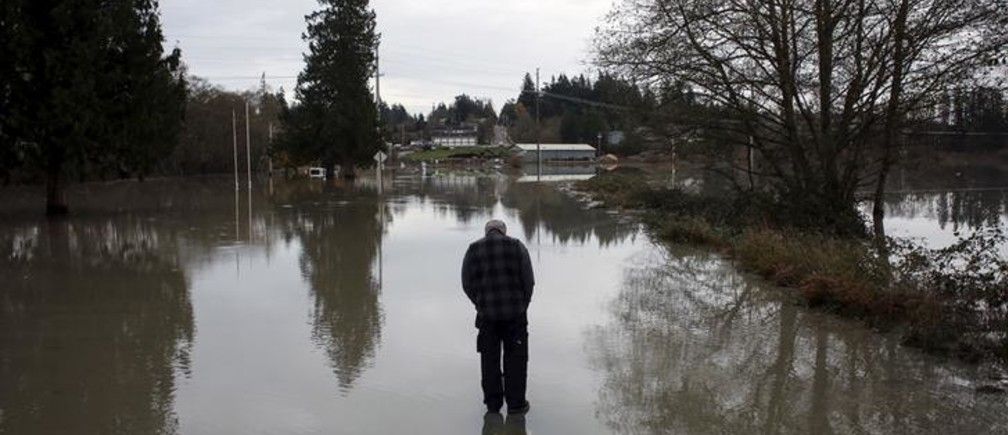 Andrew Culver observes the flooded waters of the Stillaguamish River, which overtook a roadway in Stanwood, Washington November 18, 2015. At least three people were killed and about 250,000 homes and businesses were without power in Washington state on Wednesday after a storm blew down trees and triggered mudslides, authorities said. REUTERS/David Ryder