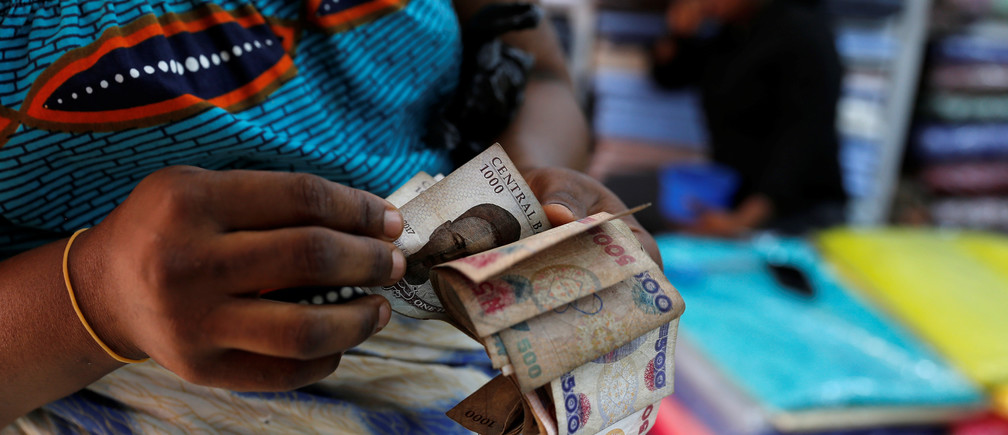 A customer counts money inside a textile shop in Idumota Market, in Nigeria's commercial capital of Lagos, Nigeria February 11, 2019. REUTERS/Nyancho NwaNri - RC1A016FA600