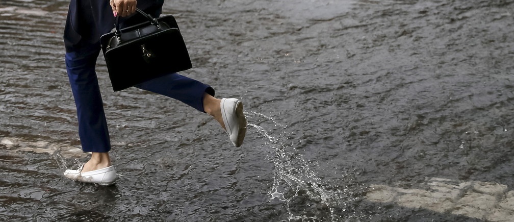 A woman jumps over a puddle as she crosses a street after rain in Kiev, Ukraine, July 14, 2015.