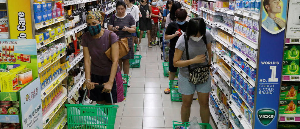 People stand behind markers as they practice social distancing while queueing up to buy food at a supermarket, during the outbreak of coronavirus disease (COVID-19), in Singapore April 3, 2020. REUTERS/Edgar Su - RC2TWF9MA32Z