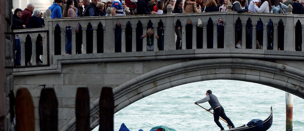 Tourists walk on a bridge as a gondolier rows his gondola near St.Marks Square in Venice, Italy, April 2, 2019. REUTERS/Guglielmo Mangiapane TPX IMAGES OF THE DAY - RC1BF90441E0
