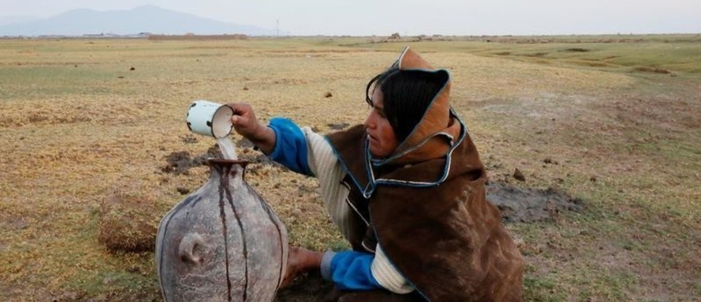 An Uru Chipaya woman pours water from a well into a jar in Chipaya , Bolivia, January 31, 2018. Picture taken January 31, 2018. REUTERS/David Mercado - RC16B0F79800