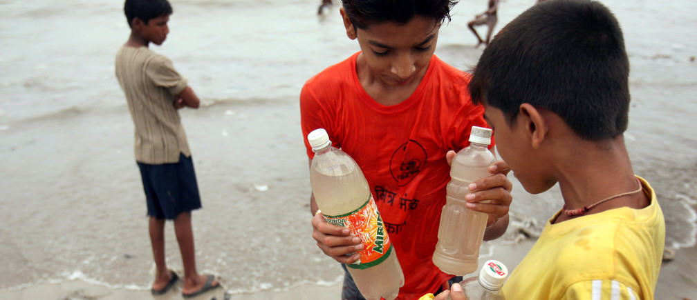 Children hold plastic bottles filled with sea water on a beach in Mumbai August 19, 2006. Thousands of Indians drank from a murky Arabian Sea creek after news spread overnight that its water had miraculously turned sweet and could cure illnesses, police said on Saturday.  REUTERS/Punit Paranjpe  (INDIA) - RTR1GI1L