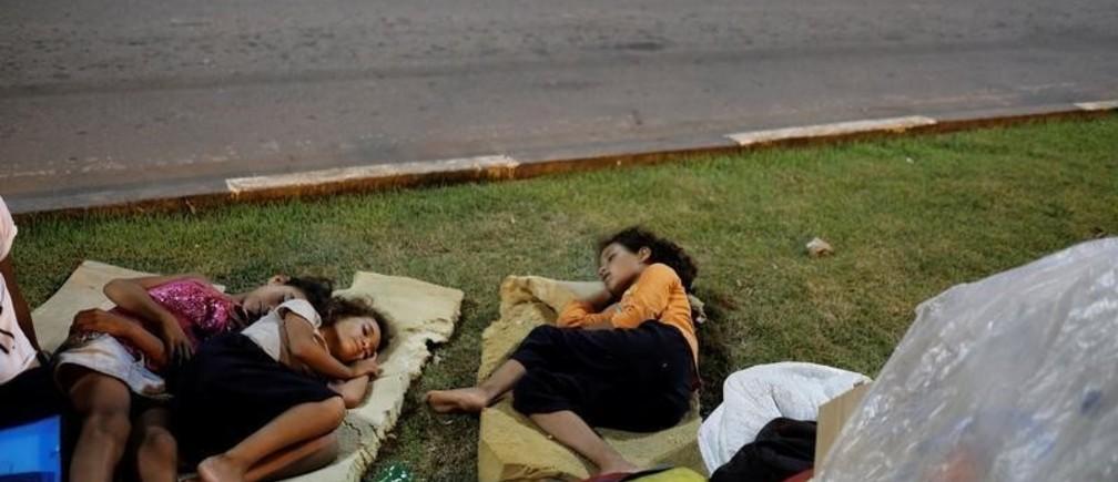 Venezuelan children sleep on the grass in front of interstate Bus Station in Boa Vista, Roraima state, Brazil August 23, 2018. Picture taken August 23, 2018.
