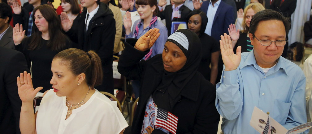 Isatu Barrie (C) raises her hand while taking the United States Oath of Citizenship during a naturalization ceremony in the Brooklyn borough of New York December 15, 2015. REUTERS/Lucas Jackson - RTX1YV2D